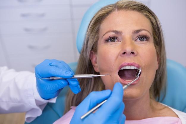 Médecin donnant un traitement dentaire à la femme à la clinique