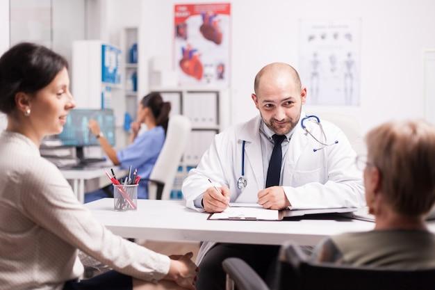 Un médecin donne de bonnes nouvelles à une femme âgée handicapée en fauteuil roulant et à sa fille lors d'un contrôle médical périodique au bureau de l'hôpital. jeune médecin expliquant le diagnostic.