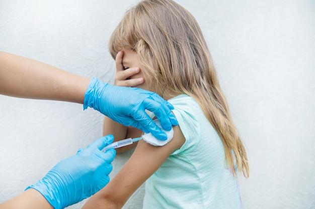 Le médecin donne à l'enfant une injection dans le bras