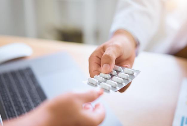 Le médecin donne des médicaments au patient pour soulager la douleur.