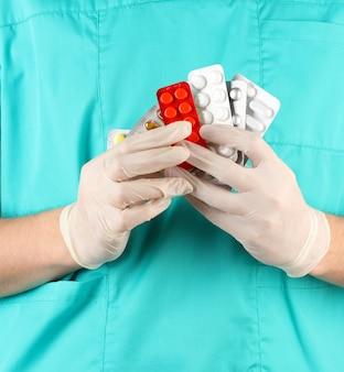 Médecin donne de nombreuses pilules différentes, isolé sur blanc