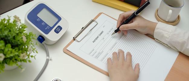Médecin écrit sur le dossier du patient assis à la table de travail dans la salle d'examen