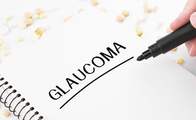 Le médecin écrit le mot glaucome sur un bloc-notes blanc