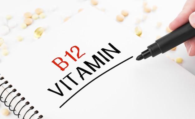 Médecin écrit le mot vitamine b12 sur un bloc-notes blanc