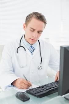 Médecin écrit une note lors de l'utilisation d'un ordinateur au cabinet médical