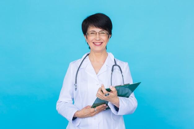 Médecin écrit une ordonnance sur un mur bleu avec copyspace