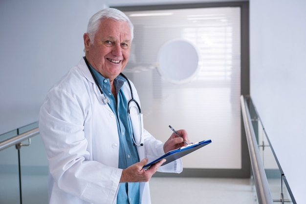 Médecin écrit sur le presse-papiers dans le passage à l'hôpital