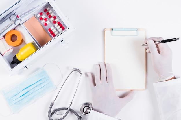 Médecin écrit sur presse-papiers avec des équipements médicaux sur fond blanc