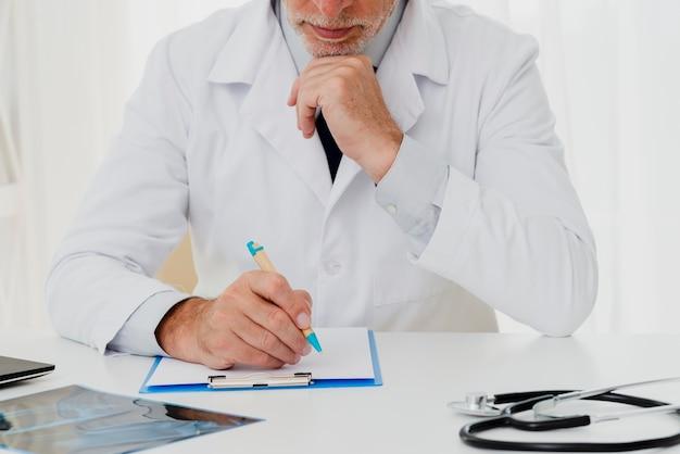Médecin écrit sur le presse-papiers avec la main sur le menton