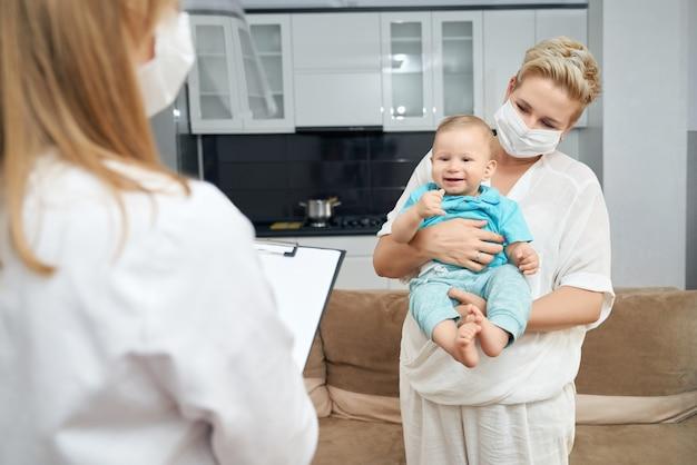 Médecin écrit sur le presse-papiers tandis que mère tenant son fils