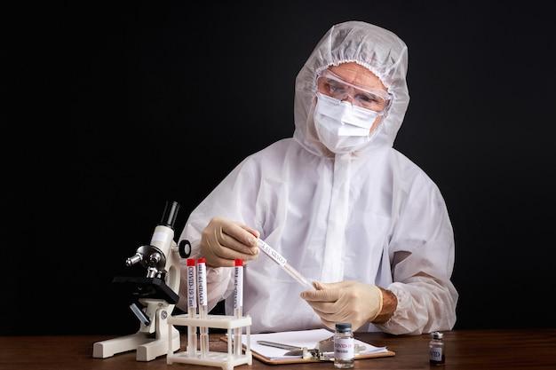Un médecin effectue des recherches à l'aide d'un tube de sang pour le test du coronavirus covid-19 ou ncov, portant une combinaison de protection isolée sur un espace noir