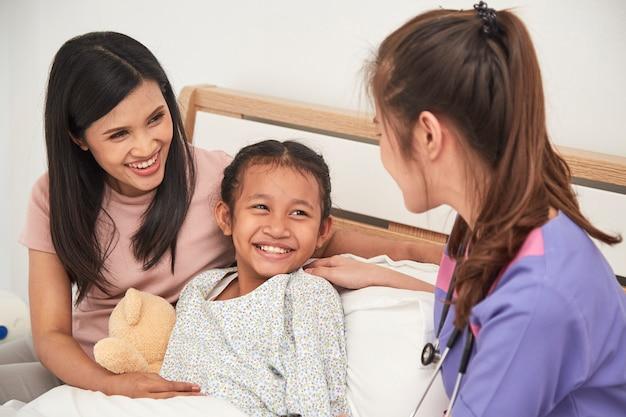 Médecin et enfant avec la mère à l'hôpital