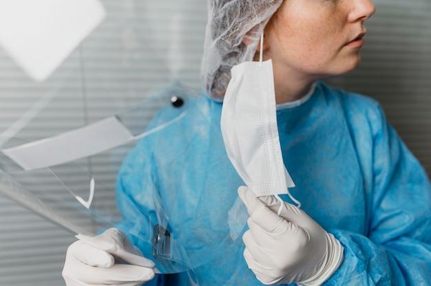 Médecin enlevant son masque facial