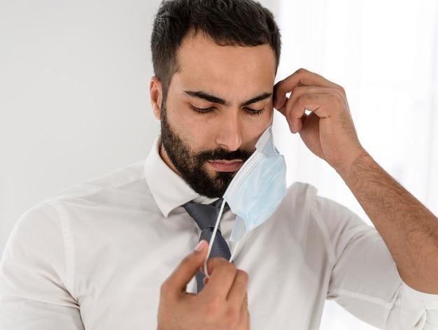 Médecin enlevant son masque médical