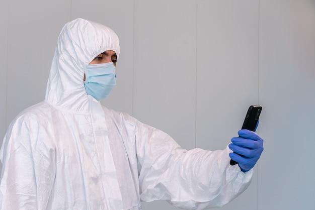 Médecin en epi consultant une application mobile sur smartphone lors d'une pandémie de covid 19 dans un hôpital d'espagne.