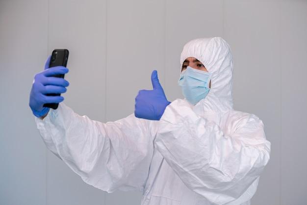 Médecin sur epi et signe un pouce en l'air tout en consultant l'application mobile sur smartphone lors d'une pandémie de covid 19. concept de télémédecine