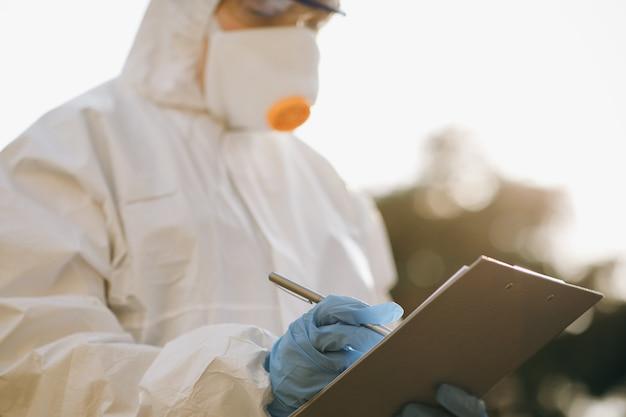 Médecin épidémiologiste combattant le coronavirus covid-19. la virologue main dans un gant blanc tient un stylo sur une feuille de papier vierge