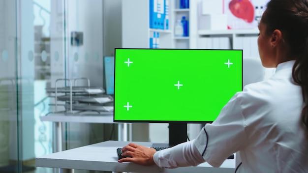 Le médecin est assis à l'ordinateur avec un écran vert vierge dans le cabinet de l'hôpital et un assistant en uniforme bleu tenant une radiographie. medic en blouse blanche travaillant sur moniteur avec clé chroma dans l'armoire de la clinique pour che