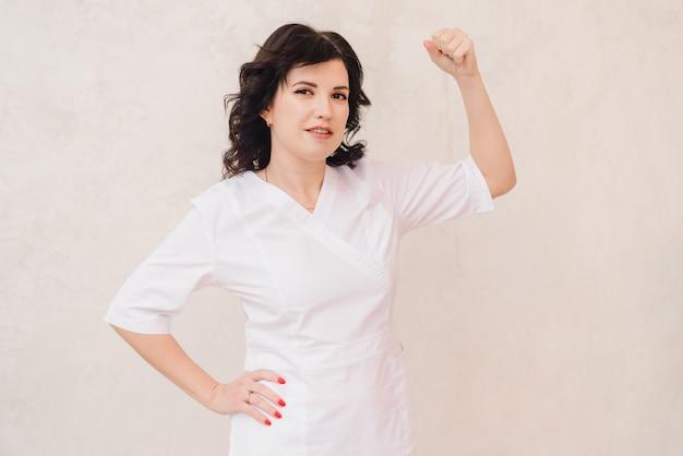 Médecin esthéticienne mignon dans une robe médicale rose et blanche regarde la caméra et montre un signe de force, de muscle.