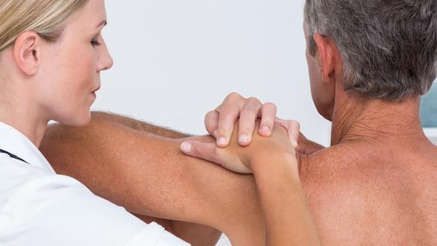 Médecin examinant son épaule patiente