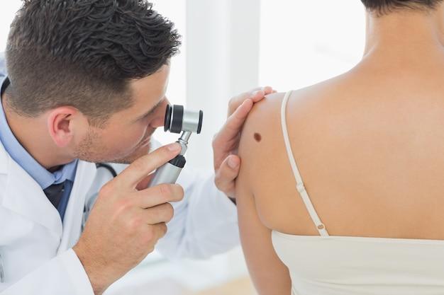 Médecin examinant la taupe sur le dos de la femme