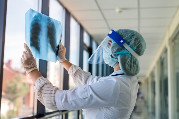 Un médecin examine l'image aux rayons x des poumons dans un écran facial et un masque pour déterminer la pneumonie causée par un nouveau virus covid19