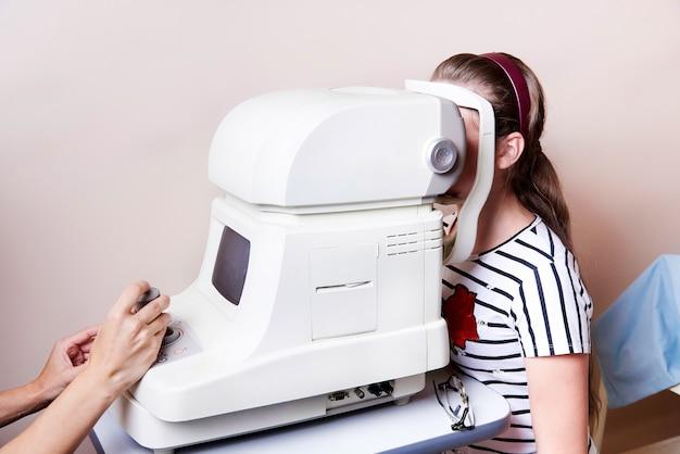 Un médecin examine les yeux de l'enfant avec un kératomètre