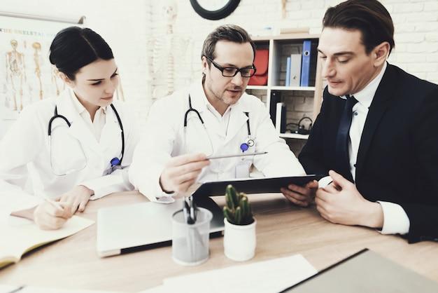 Médecin expérimenté conseille un homme d'affaires en cabinet médical.