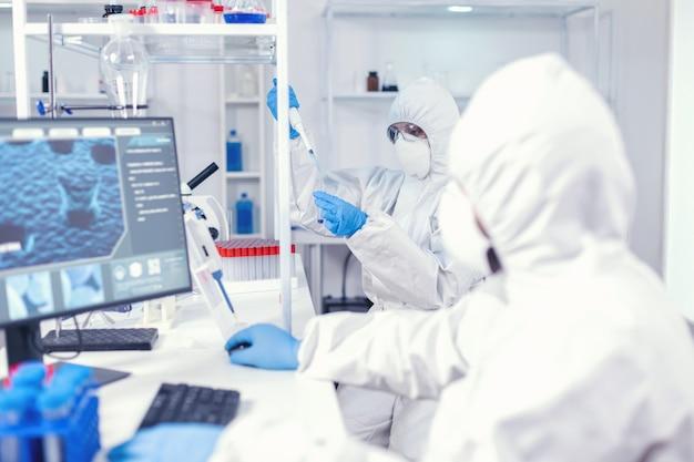 Médecin expérimenté prélevant un échantillon du tube à essai à l'aide d'une micropipette portant une combinaison stérile. équipe de microbiologistes dans un laboratoire de recherche menant une expérience pendant une pandémie mondiale avec covid19.