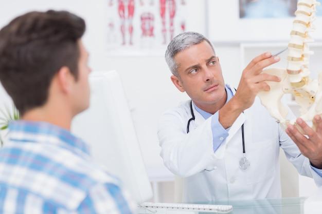 Médecin expliquant la colonne vertébrale anatomique à son patient dans un cabinet médical
