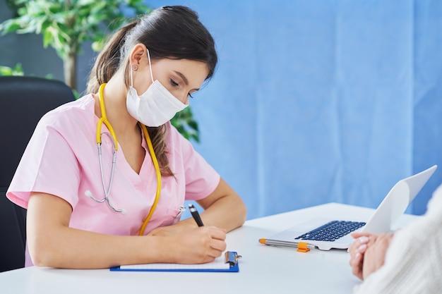 Médecin expliquant le diagnostic à sa patiente portant un masque