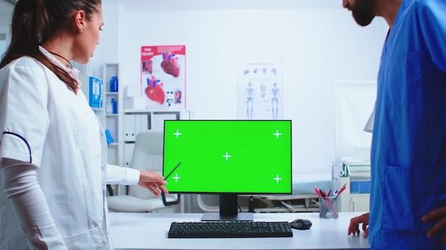 Médecin expliquant sur ordinateur avec écran vert dans le cabinet de l'hôpital à l'infirmière en uniforme bleu. medic portant une blouse blanche en clinique pointant sur le bureau avec une clé chroma parlant avec une infirmière à propos du patient di