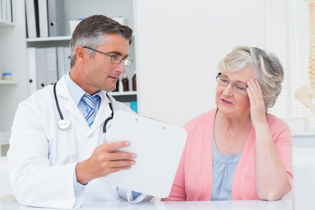 Médecin expliquant les prescriptions à une femme âgée tendue