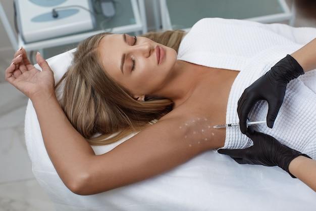 Le médecin fait des injections intramusculaires de toxine botulique dans la zone des aisselles contre l'hyperhidrose.