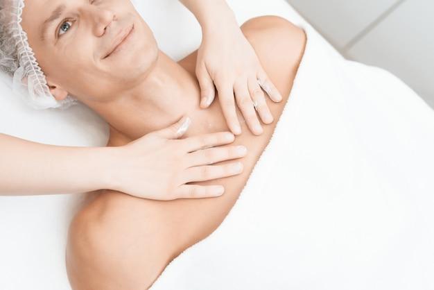 Le médecin fait un massage et étend la crème sur le visage