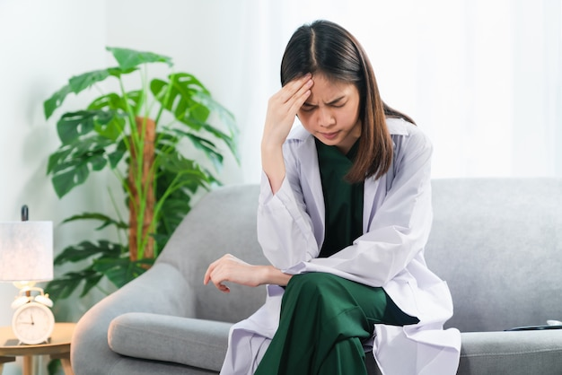 Médecin fatigué assis sur le canapé à la maison