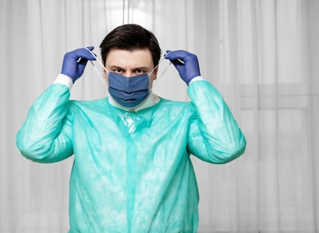 Un médecin fatigué en équipement de protection à la maison met un masque médical de protection, une épidémie de coronavirus