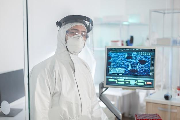 Médecin fatigué en tenue de protection contre le covid-19, l'air épuisé devant la caméra derrière le mur de verre travaillant dans une zone dangereuse