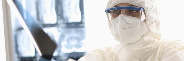 Médecin fatigué en tenue de protection et gants en caoutchouc de l'emplacement avec radiographie dans ses mains en clinique