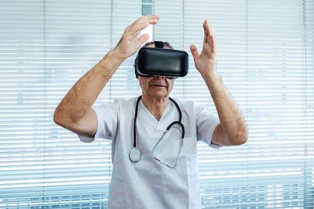 Médecin à la fenêtre d'un hôpital, utilisant des lunettes de réalité virtuelle à des fins médicales, touchant quelque chose de virtuel avec ses mains