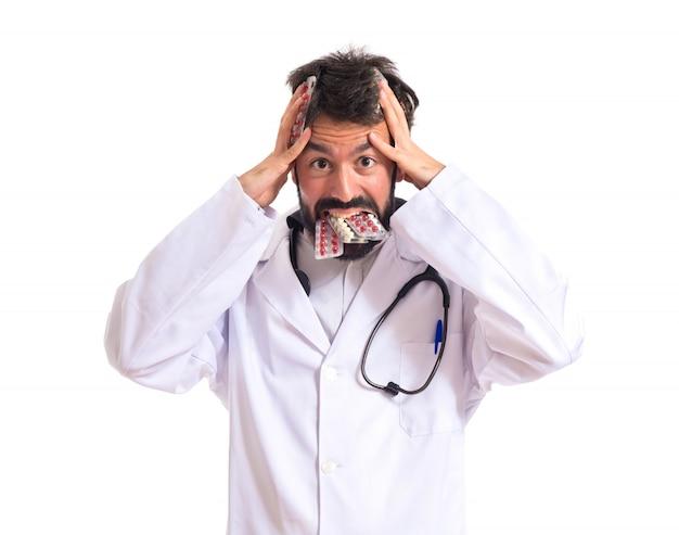 Médecin frustré avec des pilules sur fond blanc