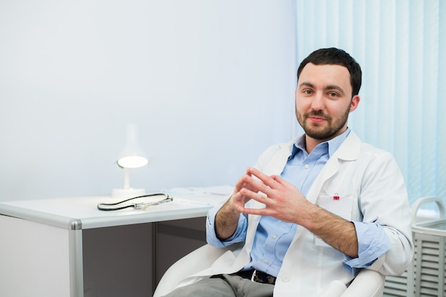 Médecin gai parler et regarder. médecin en conversation avec le patient assis à l'hôpital.