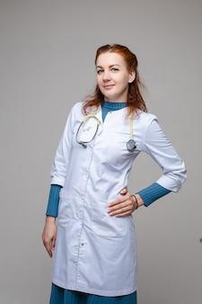 Médecin gai en vêtements médicaux avec phonendoscope autour du cou dans une robe blanche recommande de se soucier de votre santé, photo isolée sur un espace blanc