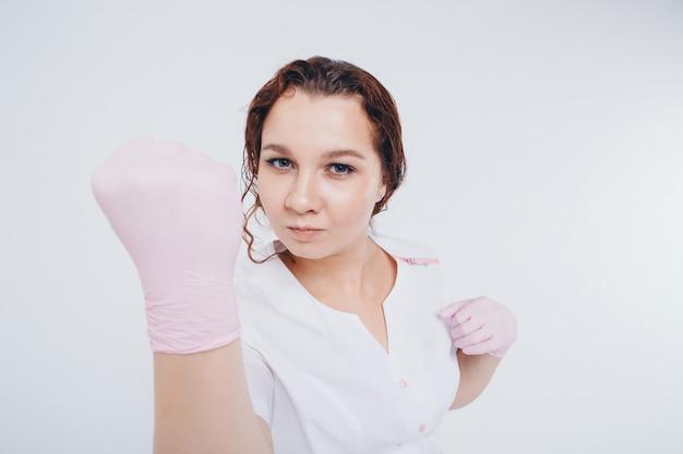 Un médecin ganté de caoutchouc menace de son poing. une fille porte un équipement de protection lors d'une épidémie. annonces d'antiseptiques et de matériel médical sur fond blanc.