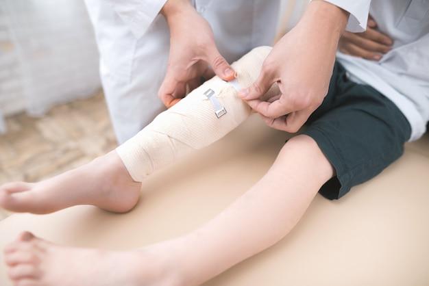 Le médecin en gants blancs rembobine sa jambe avec un bandage.
