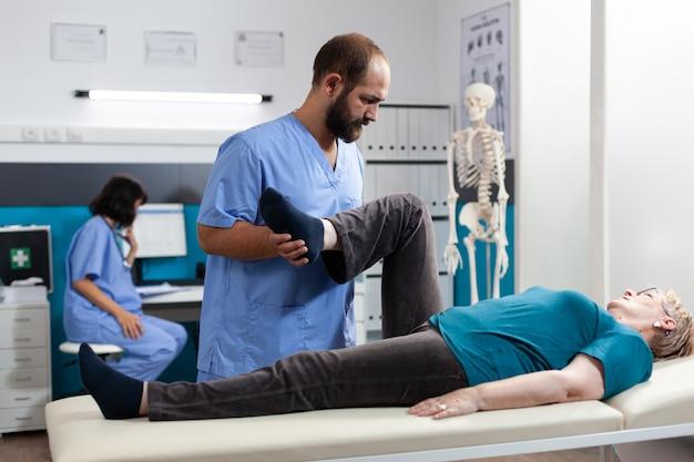 Médecin généraliste aidant une femme à la retraite souffrant de douleurs articulaires