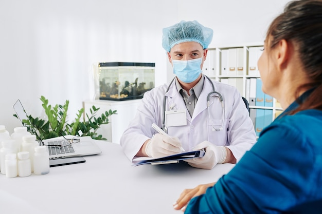 Médecin généraliste dans le document de remplissage de masque médical lors de la prise au patient dans son bureau