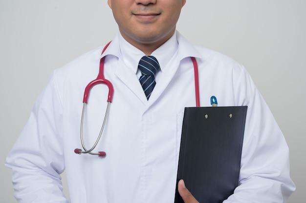 Médecin de gros plan moyen en blouse blanche, stéthoscope tenant le presse-papiers vers le bras
