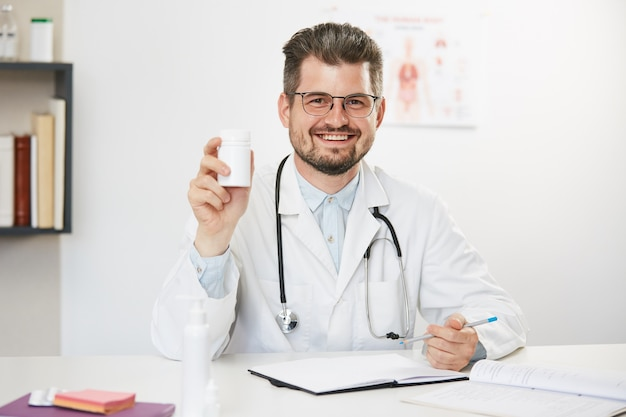 Médecin heureux montrant pot de pilules avec sourire sur le visage, thérapeute masculin barbu en uniforme médical blanc avec stéthoscope assis dans le cabinet médical et montrant le pot avec des pilules