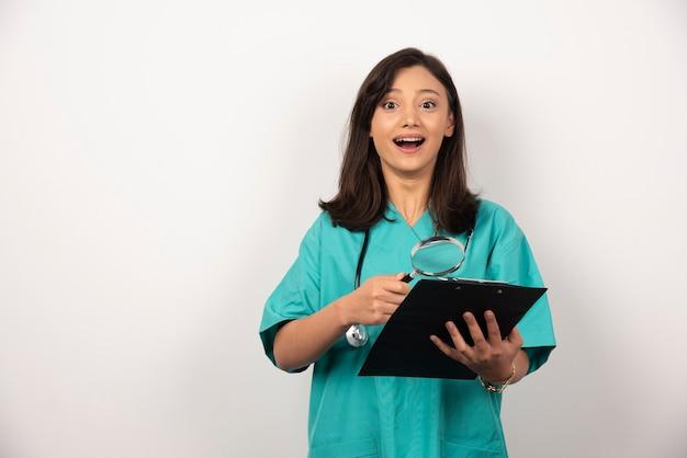 Médecin heureux avec presse-papiers et loupe sur fond blanc. photo de haute qualité